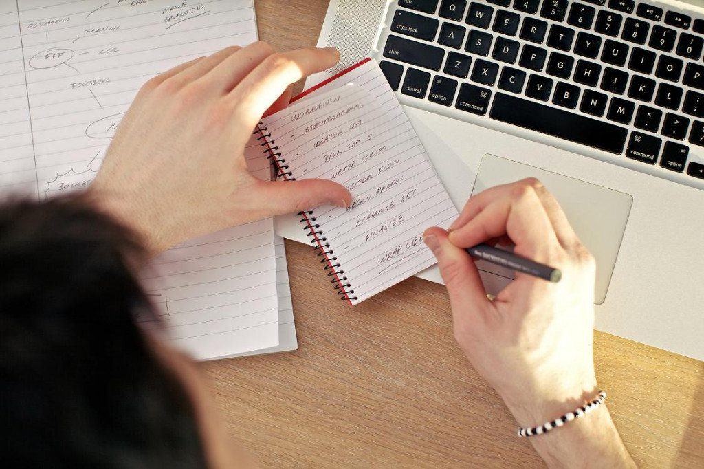 Overhead view of a mans hands writing in a notebook balanced on a laptop keyboard.