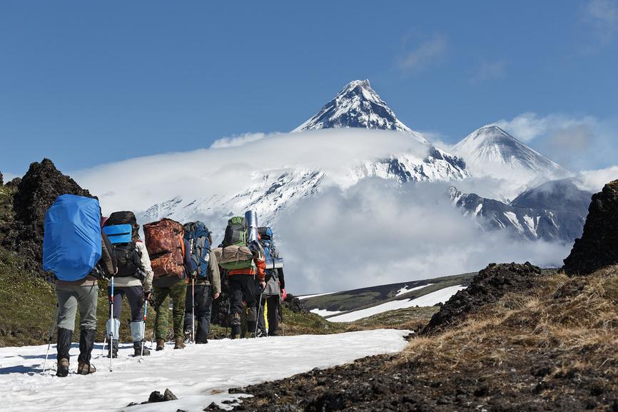 Тургруппа идет в горах на фоне вулканов. Камчатка, Ключевская группа вулканов © А. А. Пирагис / Фотобанк Лори